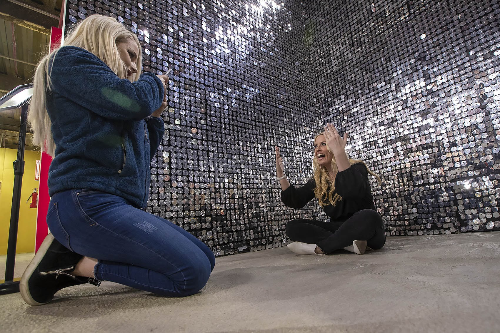"""Caroline Gray takes a photo of Sarah Russo with her phone in the glittery space at """"Happy Place."""" (Jesse Costa/WBUR)"""