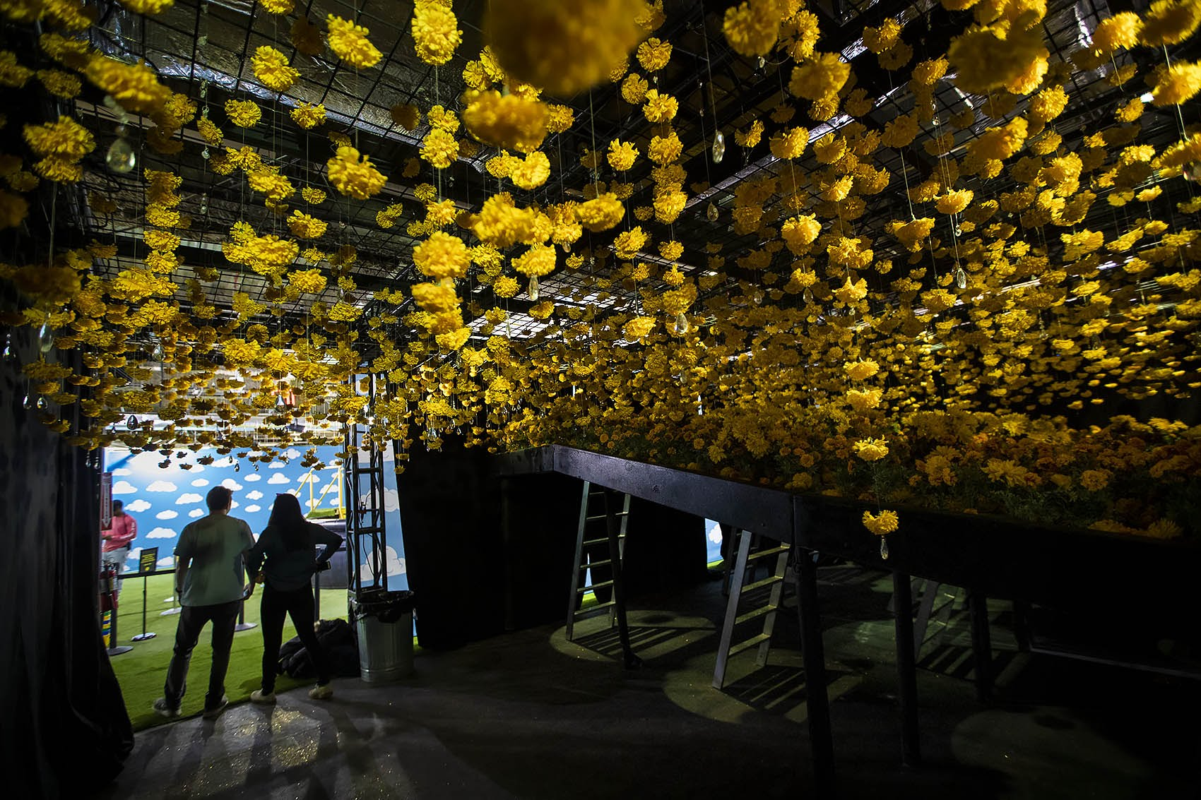 """Riley Bates and Madison Munoz walk out of a room with hundreds yellow carnations hanging from the ceiling at """"Happy Place."""" (Jesse Costa/WBUR)"""