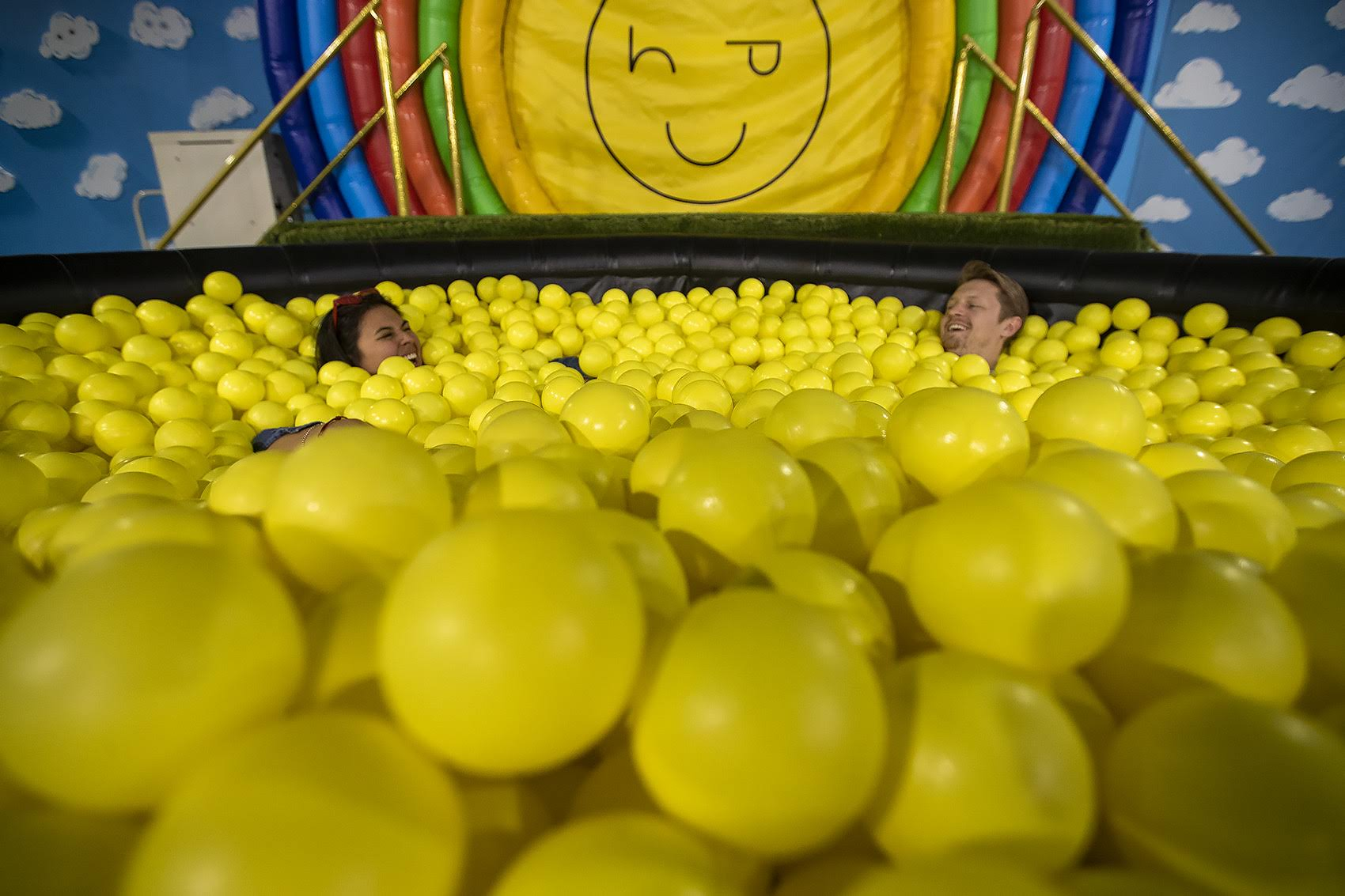 "Madison Munoz and Riley Bates enjoy themselves in the pool of yellow balls at ""Happy Place."" (Jesse Costa/WBUR)"