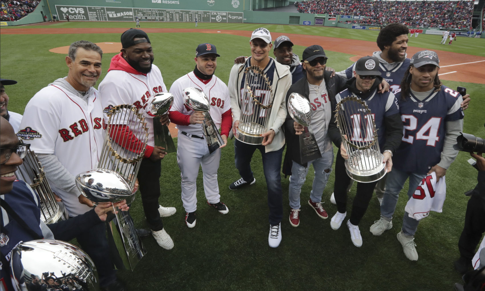 2f2c32bbf Patriots and Red Sox players hold Super Bowl and World Series trophies.  From left they