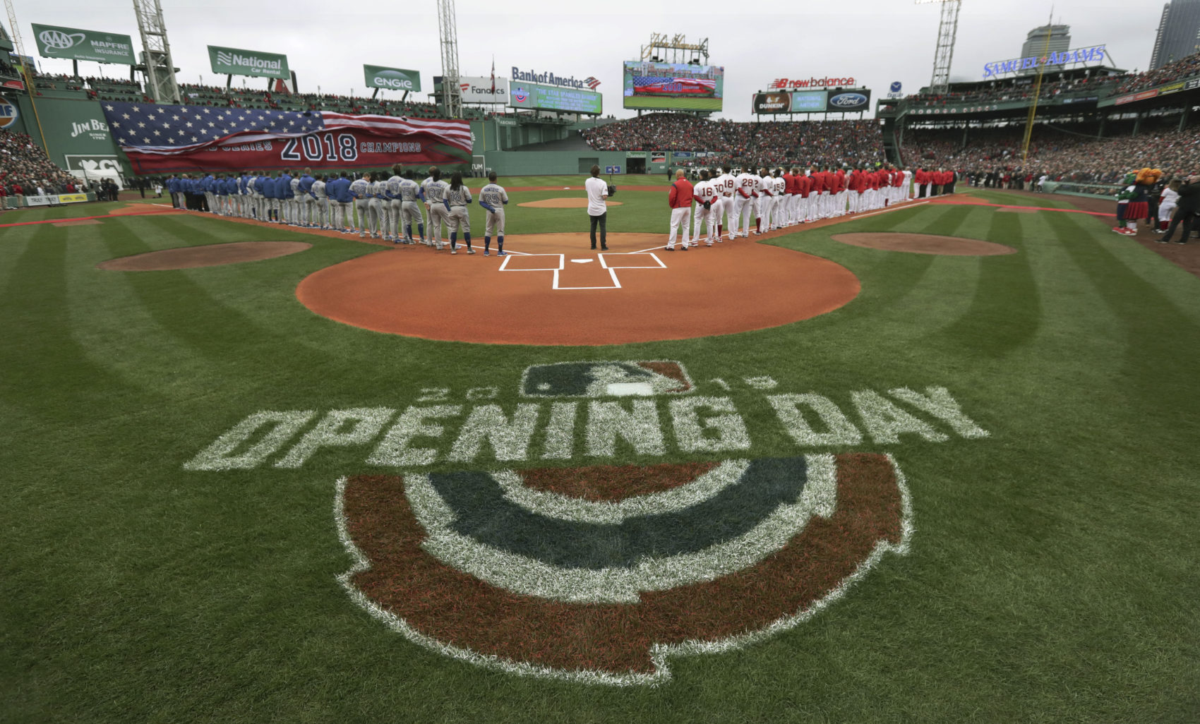 The Toronto Blue Jays, left, and Boston Red Sox stand along the base lines during the national anthem before the home opener baseball game on Tuesday in Boston. (Charles Krupa/AP)