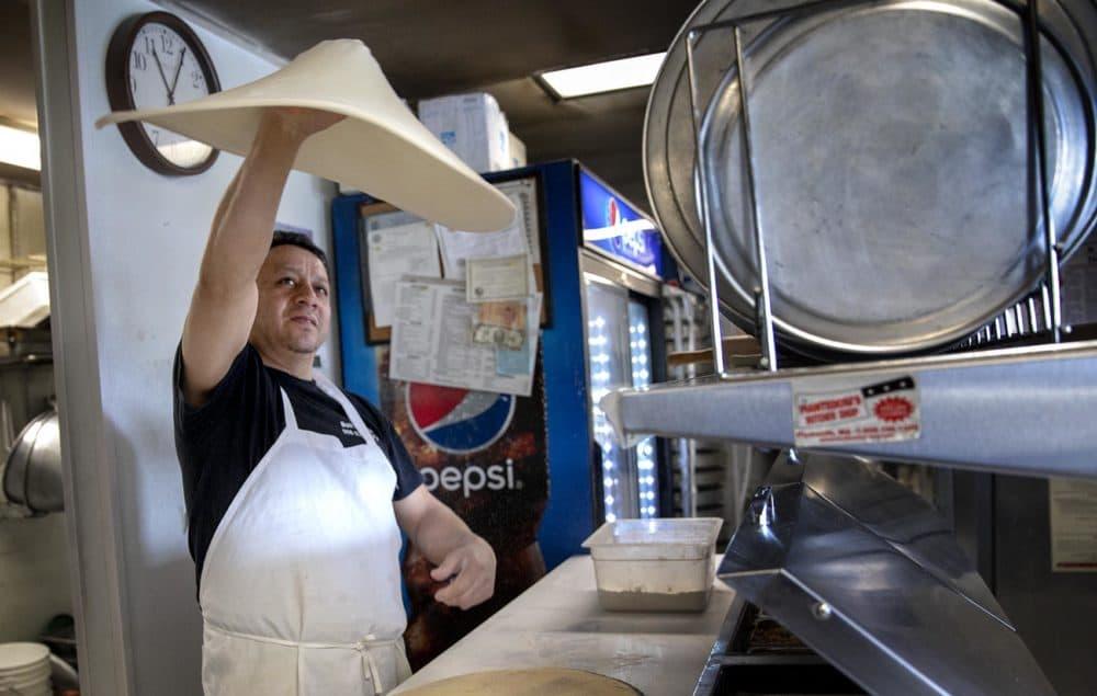 Boli Matute, owner of Boli's Pizza, tosses dough in the air. (Robin Lubbock/WBUR)