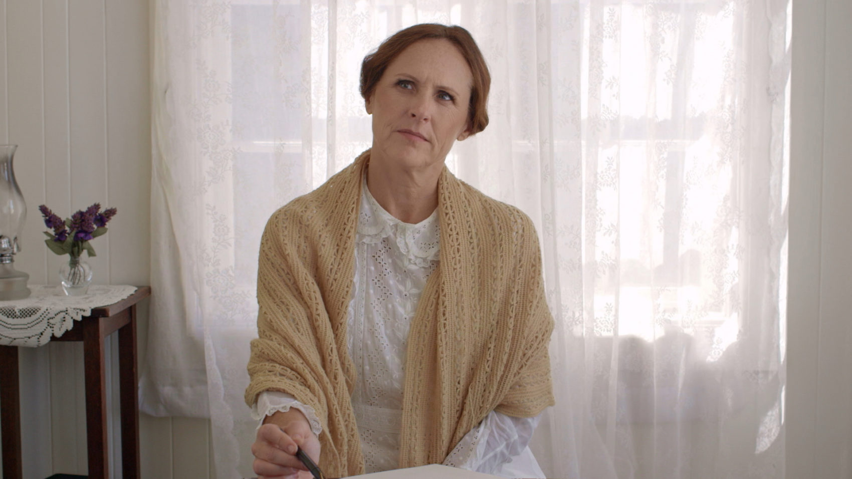 "Emily (Molly Shannon) thinks at her desk, in a still from ""Wild Nights With Emily."" (Courtesy of Greenwich Entertainment)"