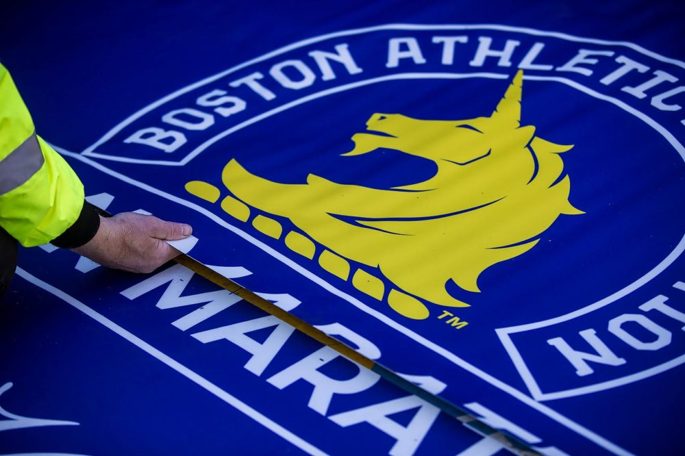Workers from Accurate Graphics lay down the finish line on Boylston Street in Copley Square for the 2019 Boston Marathon. (Jesse Costa/WBUR)