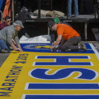 Workers lay down the finish line on Boylston Street in Copley Square for the 2019 Boston Marathon. (Jesse Costa/WBUR)