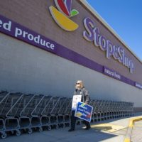 A striking Stop & Shop worker walks in front of the main entrance of the Somerville location on McGrath Highway on Thursday, when the strike began. (Jesse Costa/WBUR)