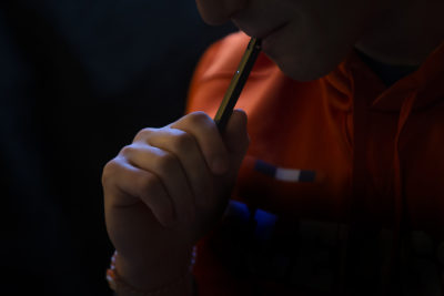 A teen uses a JUUL vaping device at home. (Jesse Costa/WBUR)