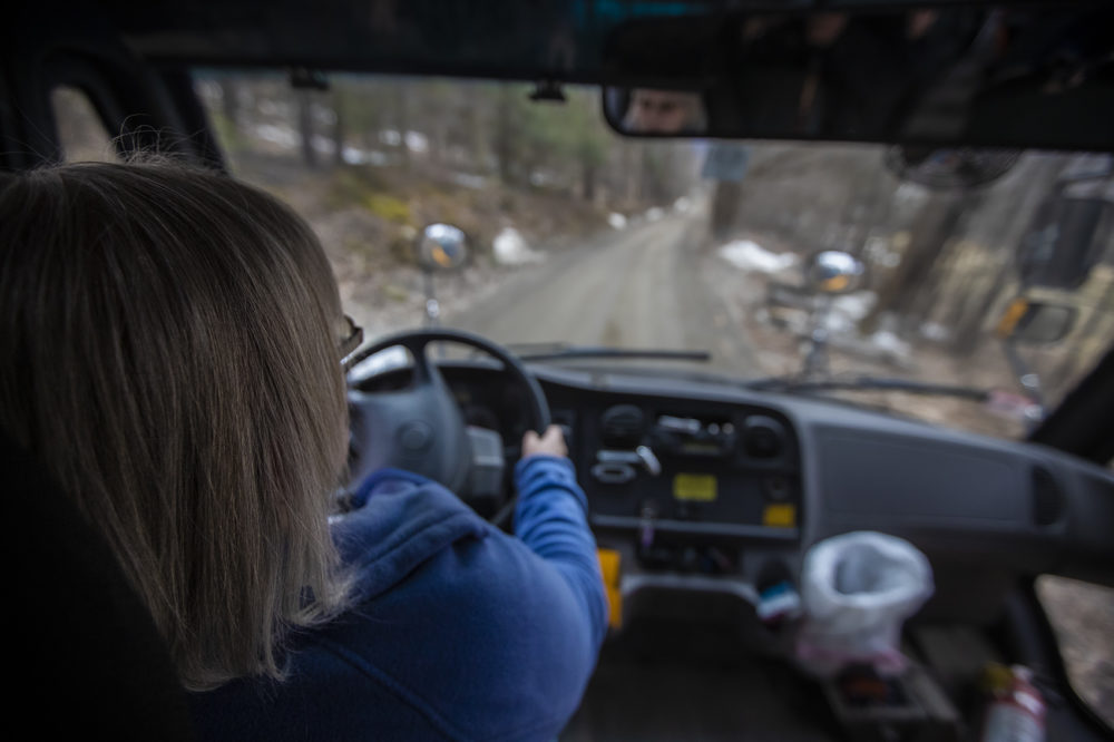 Joanne Deady drives her bus around a bend of an unpaved Thompson Road in Colrain on her route after the school day. (Jesse Costa/WBUR)