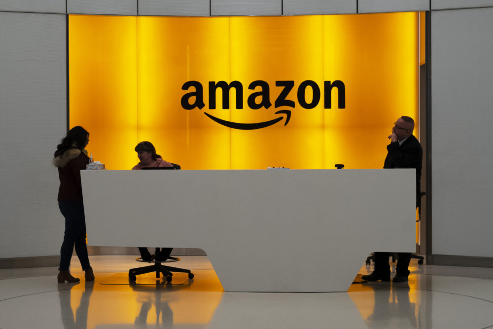 People stand in the lobby for Amazon offices Thursday, Feb. 14, 2019, in New York. Twenty-eight employees at Amazon have filed an activist shareholder proposal asking the company to take a stronger stance on climate change. (Mark Lennihan/AP)