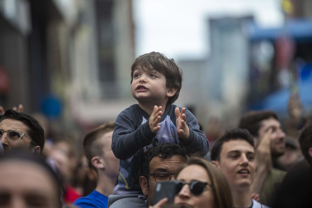 A young spectator cheers as the elite men race toward the finish line. (Jesse Costa/WBUR)