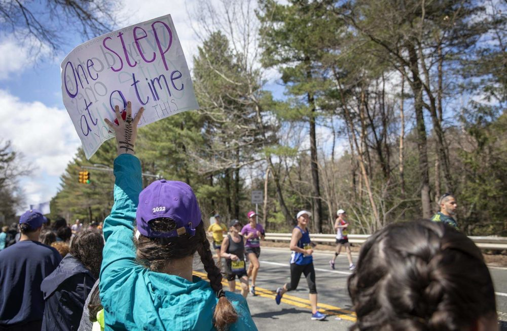 """A woman holds up a sign to encourage runners through the Wellesley """"scream tunnel."""" (Robin Lubbock/WBUR)"""