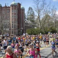 "As the sun comes out towards the middle of the day, marathon runners race through the ""scream tunnel"" at Wellesley. (Robin Lubock/WBUR)"