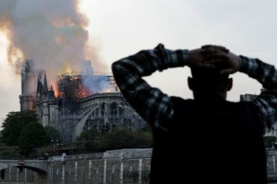 A man watches the landmark Notre Dame Cathedral burn in central Paris on April 15, 2019. (Geoffroy Van der Hasselt/AFP/Getty Images)