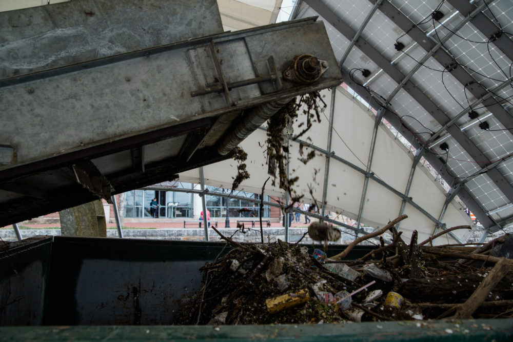 "Garbage moves along a conveyor belt into Mr. Trash Wheel's ""tum tum"" — a dumpster. (Rosem Morton for Here & Now)"