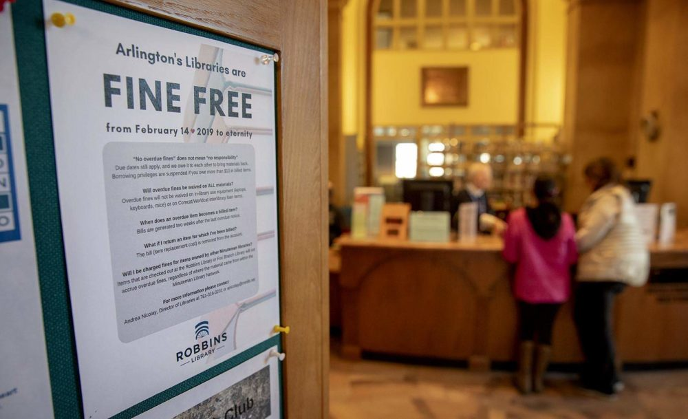 A flyer near the check-out desk explains Arlington's fine free policy. (Robin Lubbock/WBUR)