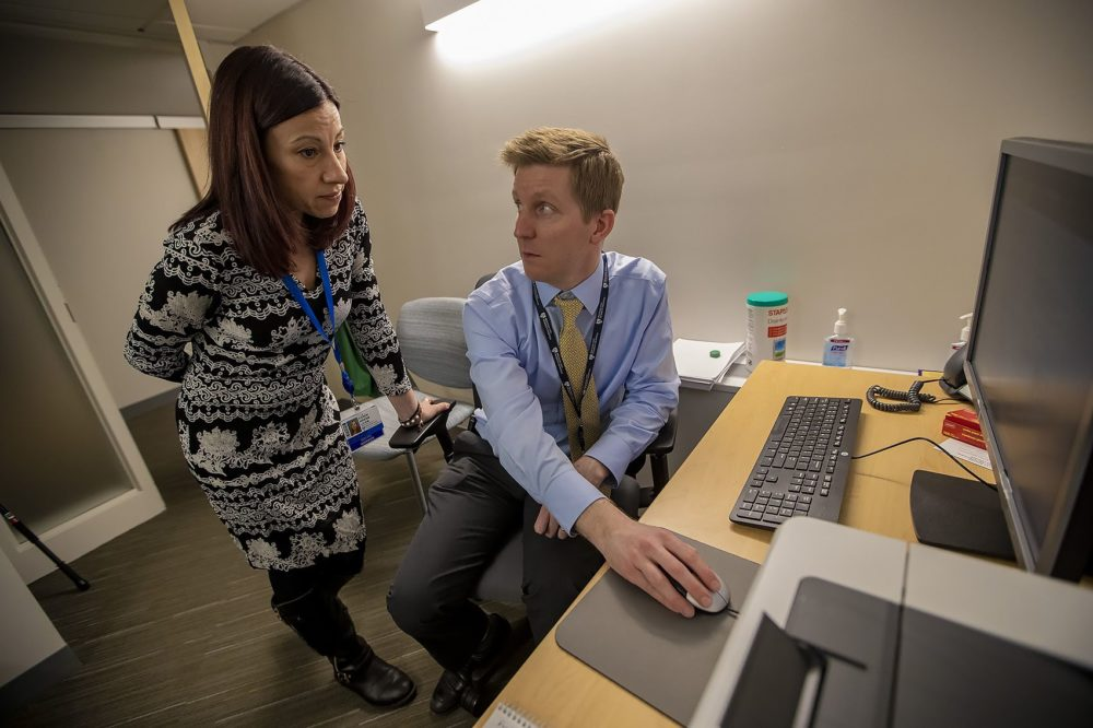 Dr. David Kroll and social worker Karen Wrenn review a patients records prior to a visit at the Brigham and Women's Psychiatric Specialties Clinic. (Jesse Costa/WBUR)