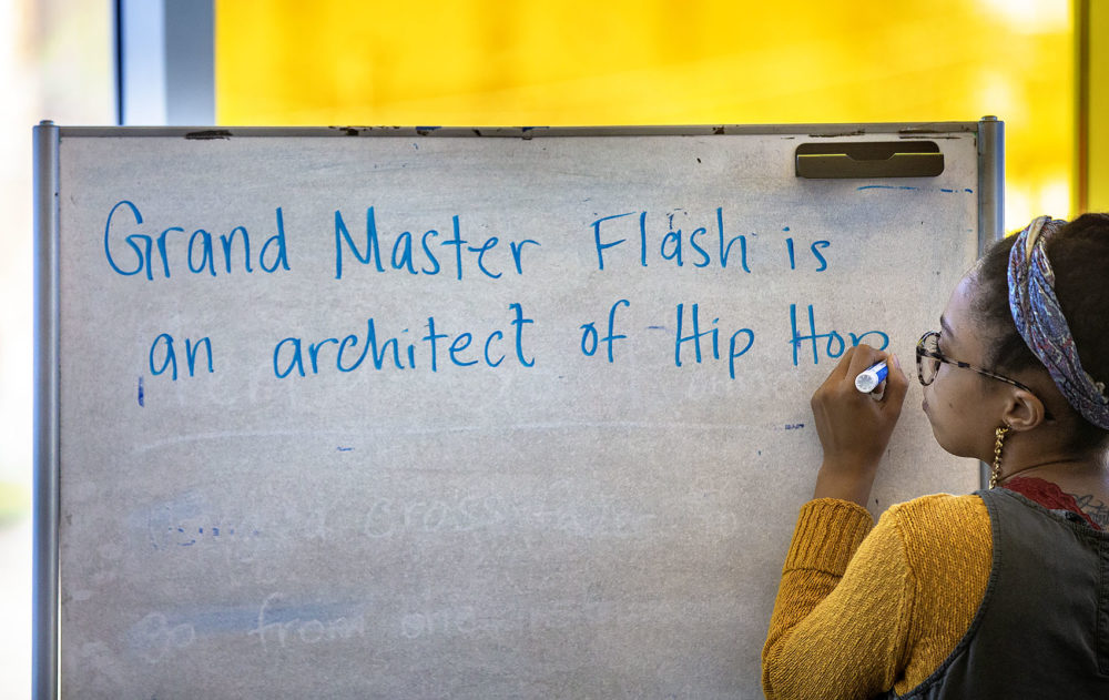 Kyara Andrade writes on a whiteboard during a workshop on hip-hop's founders this week. (Jesse Costa/WBUR)