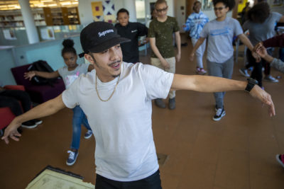 "Floor Lords Crew dancer Alex Diaz shows students a few moves during ""The Breaks"" at Grove Hall Library. (Jesse Costa/WBUR)"