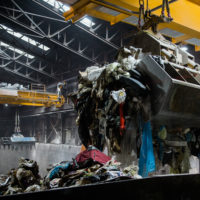 Overhead cranes transfer gathered trash into a feed hopper. The Wheelabrator processes about 2,250 tons of waste per day. (Rosem Morton for Here & Now)