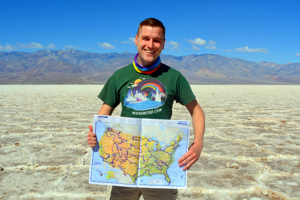 Mikah Meyer holds up a map of his journey at his 313th stop: Badwater Basin in Death Valley National Park, the lowest point in North America. (Courtesy of Mikah Meyer)