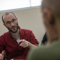 """Guy Ben-Aharon, artistic director of the Israeli Stage, talks through """"The Return"""" with actor Nael Nacer during a rehearsal. (Jesse Costa/WBUR)"""