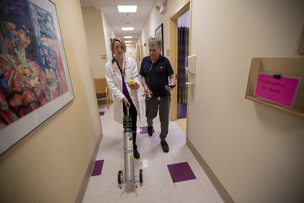 Dr. Mary Rice walks with Michael Howard, who has the progressive lung disease COPD, as they test oxygen levels with a portable tank. (Jesse Costa/WBUR)