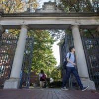 Harvard students walk through the Class of 1875 Gate in Harvard Yard. (Jesse Costa/WBUR)