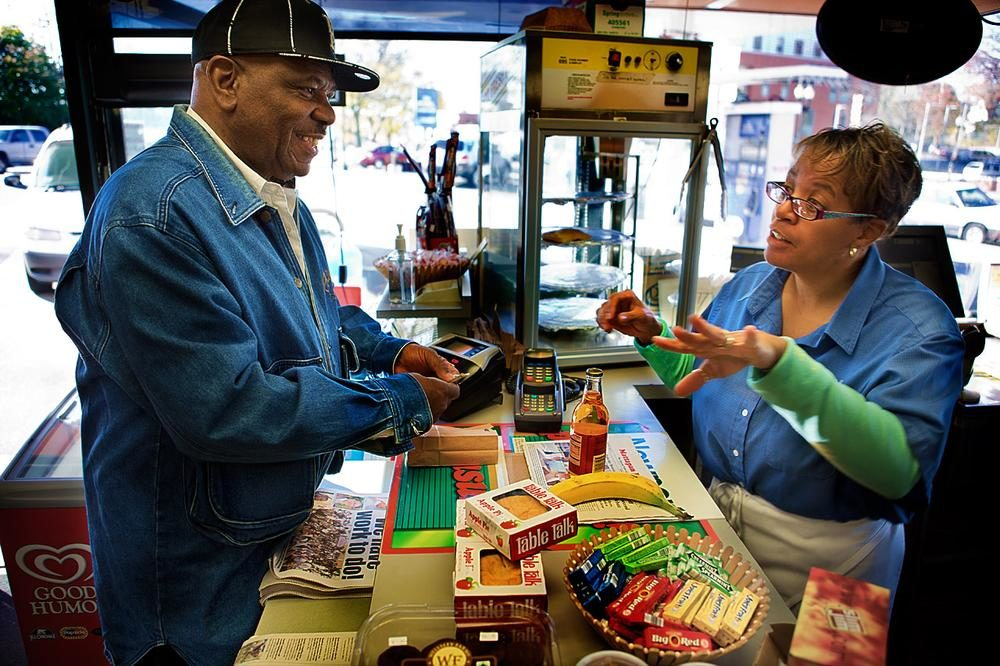 In this 2013 file photo, Stacey Thomas, right, works at the family's Mobil Station on Blue Hill Avenue in Mattapan Square. (Jesse Costa/WBUR)