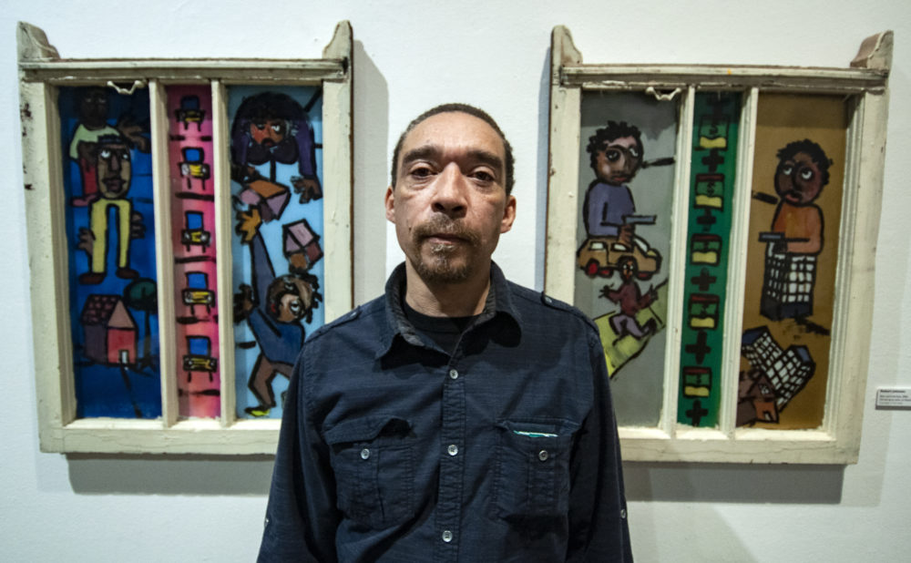 Chicago artist Robert Johnson stands in front of two of his window paintings at Intuit: The Center for Intuitive and Outsider Art in Chicago. (Chris Bentley/Here & Now)