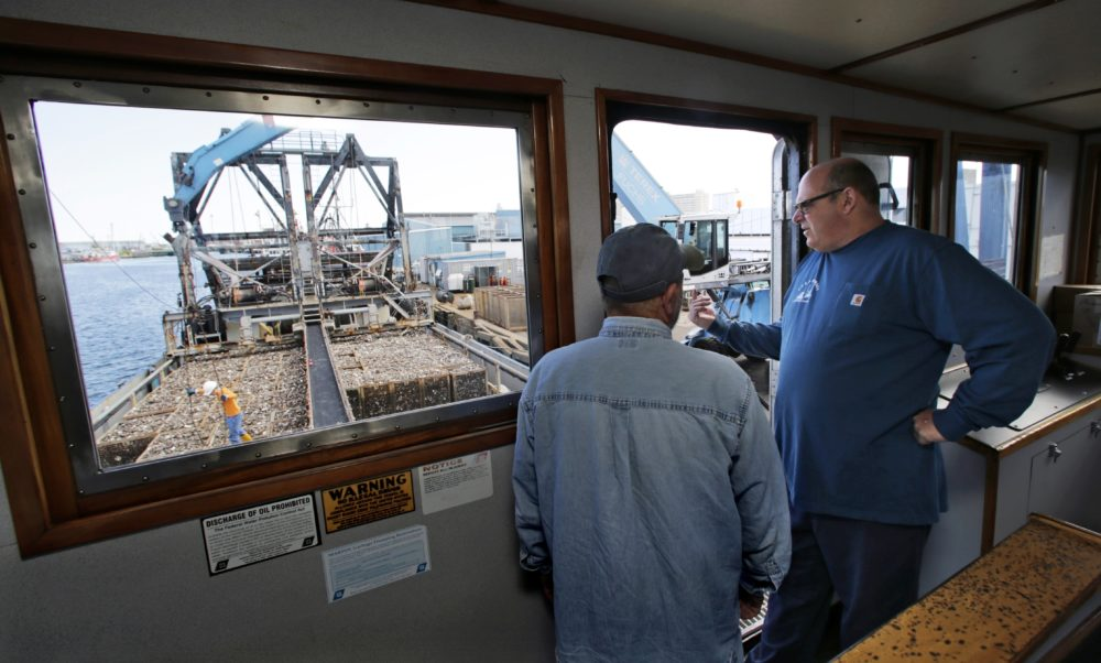 In this May 2016 photo, Mike Mohr, right, captain of the fishing vessel E.S.S. Pursuit, talks with his first mate while offloading a two-day haul of quahog clams at a dock in New Bedford, Mass. (Charles Krupa/AP)