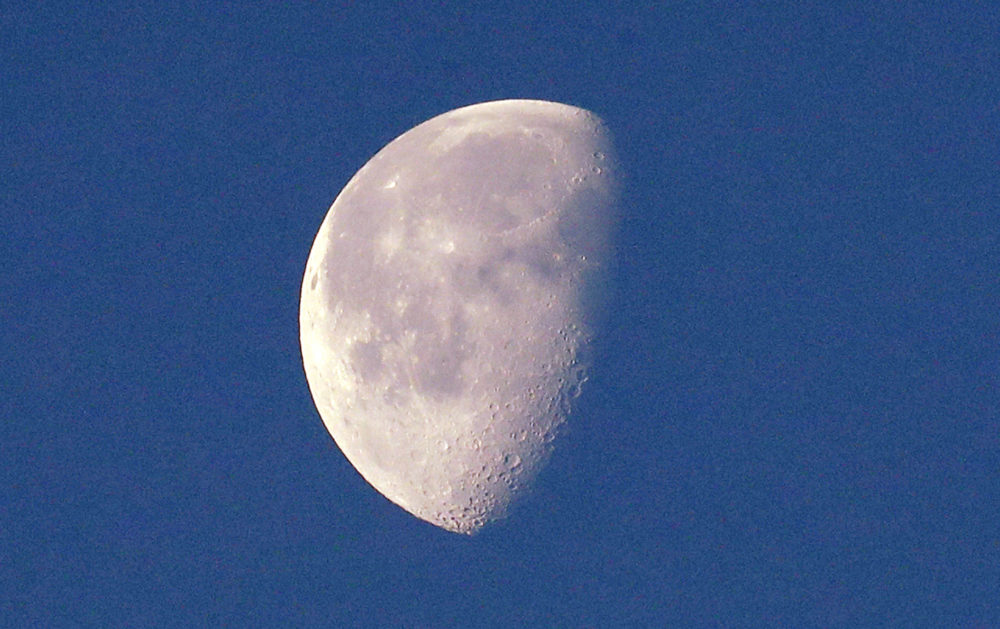 In this photo taken Dec. 27, 2018, the moon, in a waning gibbous phase and briefly visible on an otherwise cloudy day, is seen from Seattle. Despite the name of Pink Floyd's best-selling album, the side of the moon you can't see isn't always dark. But it is far. So scientists call the area where a Chinese spacecraft just landed the far side, not the dark side. (AP Photo/Elaine Thompson)