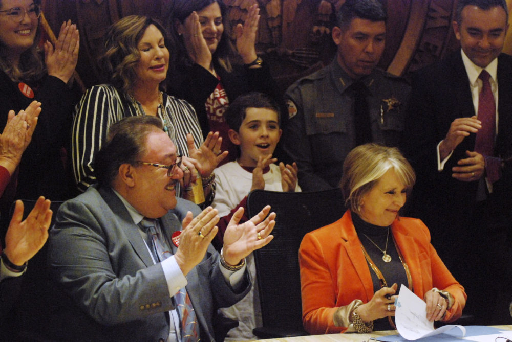 New Mexico Gov. Michelle Lujan Grisham signs a bill into law that expands background checks to nearly all gun sales in New Mexico in a ceremony in in Santa Fe, N.M., Friday, March 8, 2019. (Morgan Lee/AP)