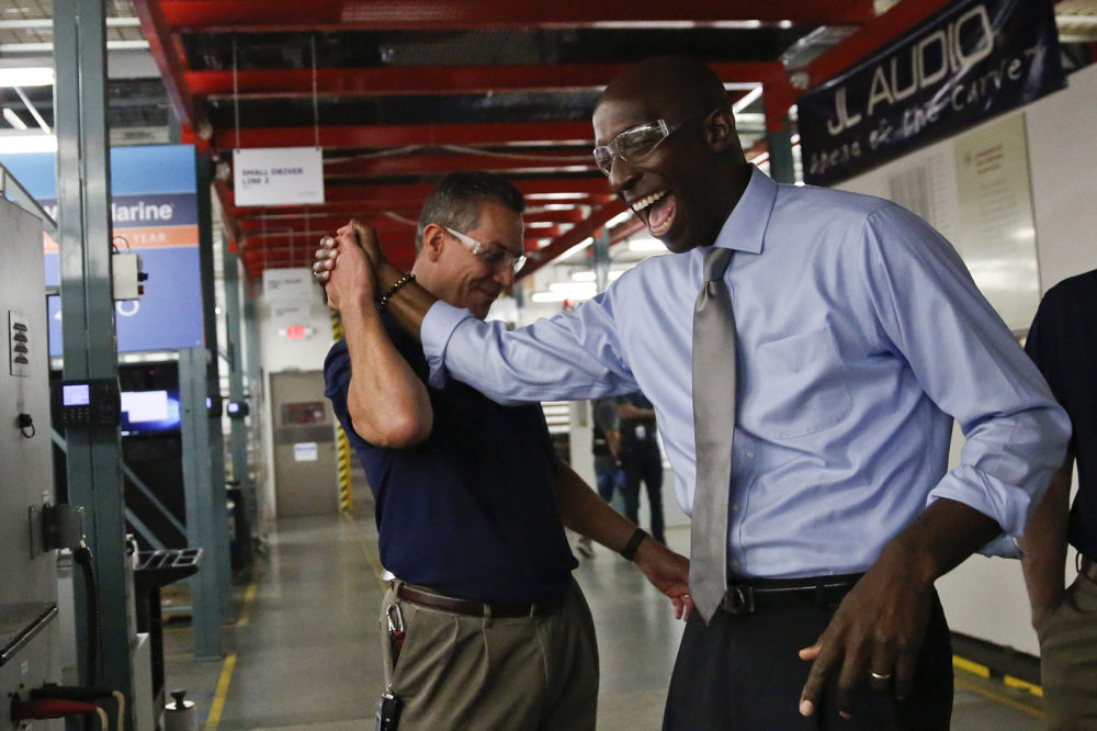 Miramar Mayor Wayne Messam, right, laughs with Stephen Turrisi, left, the director of training and technical services at JL Audio during a tour in Miramar, Fla. (Brynn Anderson/AP)