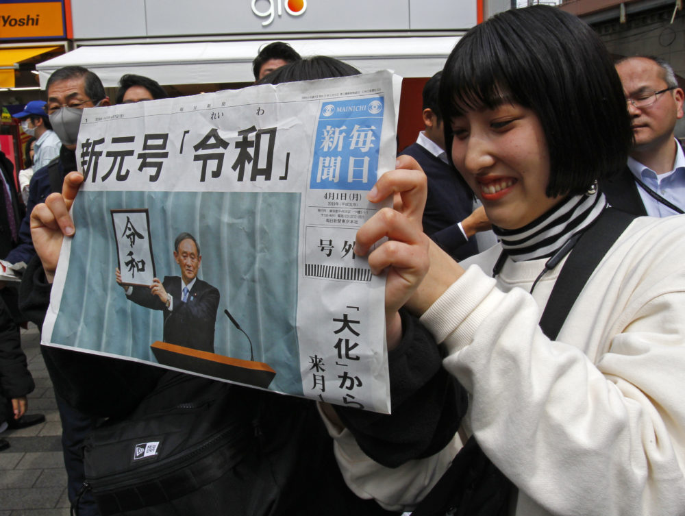 "A woman holds a copy of the Mainichi Shimbun newspaper reporting the name of new era ""Reiwa,"" unveiled in Tokyo, Monday, April 1, 2019. (Koji Sasahara/AP)"