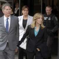 Actress Felicity Huffman departs federal court in Boston with her brother Moore Huffman Jr., left, on Wednesday, April 3, 2019, after facing charges in a nationwide college admissions bribery scandal. (Steven Senne/AP)