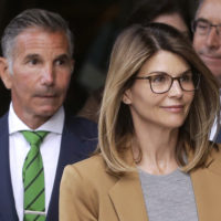 In this April 3, 2019 photo, actress Lori Loughlin, front, and husband, clothing designer Mossimo Giannulli, left, depart federal court in Boston after facing charges in a nationwide college admissions bribery scandal. (Steven Senne/AP)