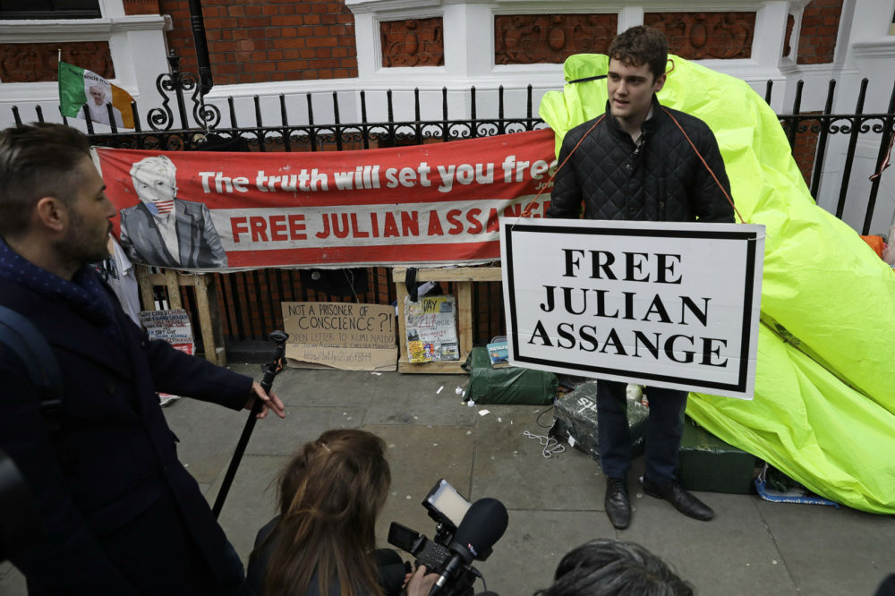 A protester holds a placard outside the Ecuadorian Embassy in London, after WikiLeaks founder Julian Assange was arrested by officers from the Metropolitan Police and taken into custody Thursday April 11, 2019. (Matt Dunham/AP)