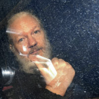 Julian Assange gestures as he arrives at Westminster Magistrates' Court in London, after the WikiLeaks founder was arrested by officers from the Metropolitan Police and taken into custody Thursday April 11, 2019. (Victoria Jones/PA via AP)