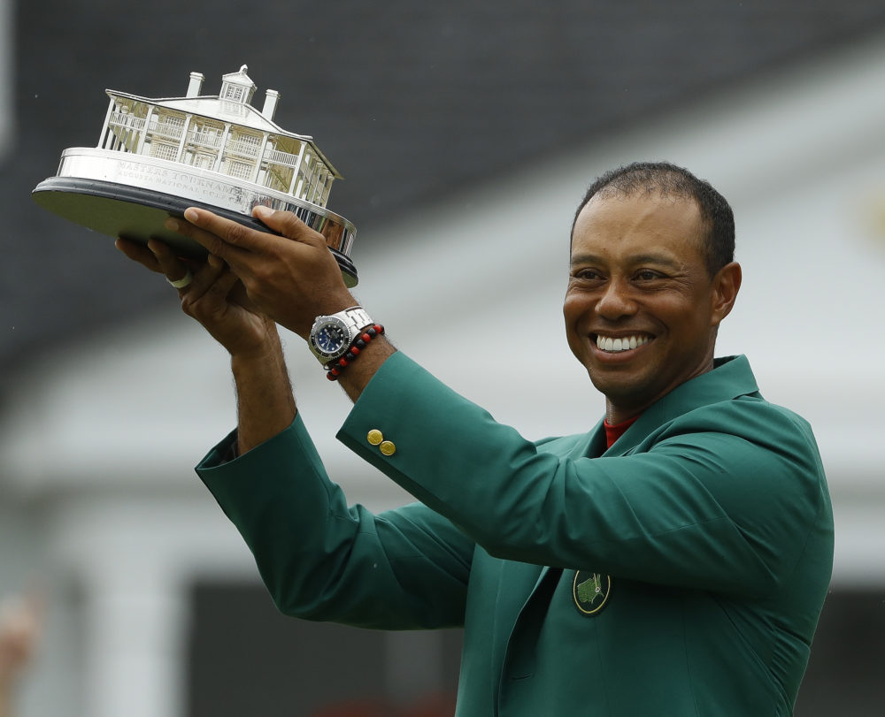 Tiger Woods wears his green jacket holding the winning trophy after the final round for the Masters golf tournament Sunday, April 14, 2019, in Augusta, Ga. (Matt Slocum/AP)