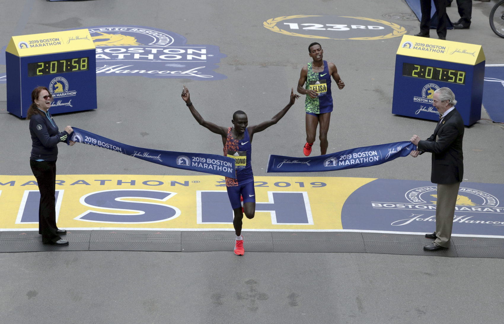 Lawrence Cherono, of Kenya, breaks the tape to win the 123rd Boston Marathon in front of Lelisa Desisa, of Ethiopia, right. (Charles Krupa/AP)