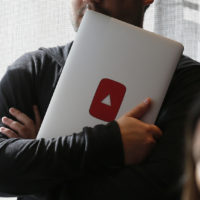 A man holds a laptop computer with a YouTube logo on it at YouTube Space LA offices Wednesday, Oct. 21, 2015, in Los Angeles. (Danny Moloshok/AP)