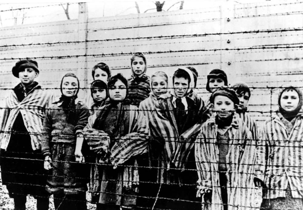 A picture taken just after the liberation by the Soviet army in January 1945, shows a group of children wearing concentration camp uniforms behind barbed wire fencing in the Auschwitz Nazi concentration camp. (AP file photo)
