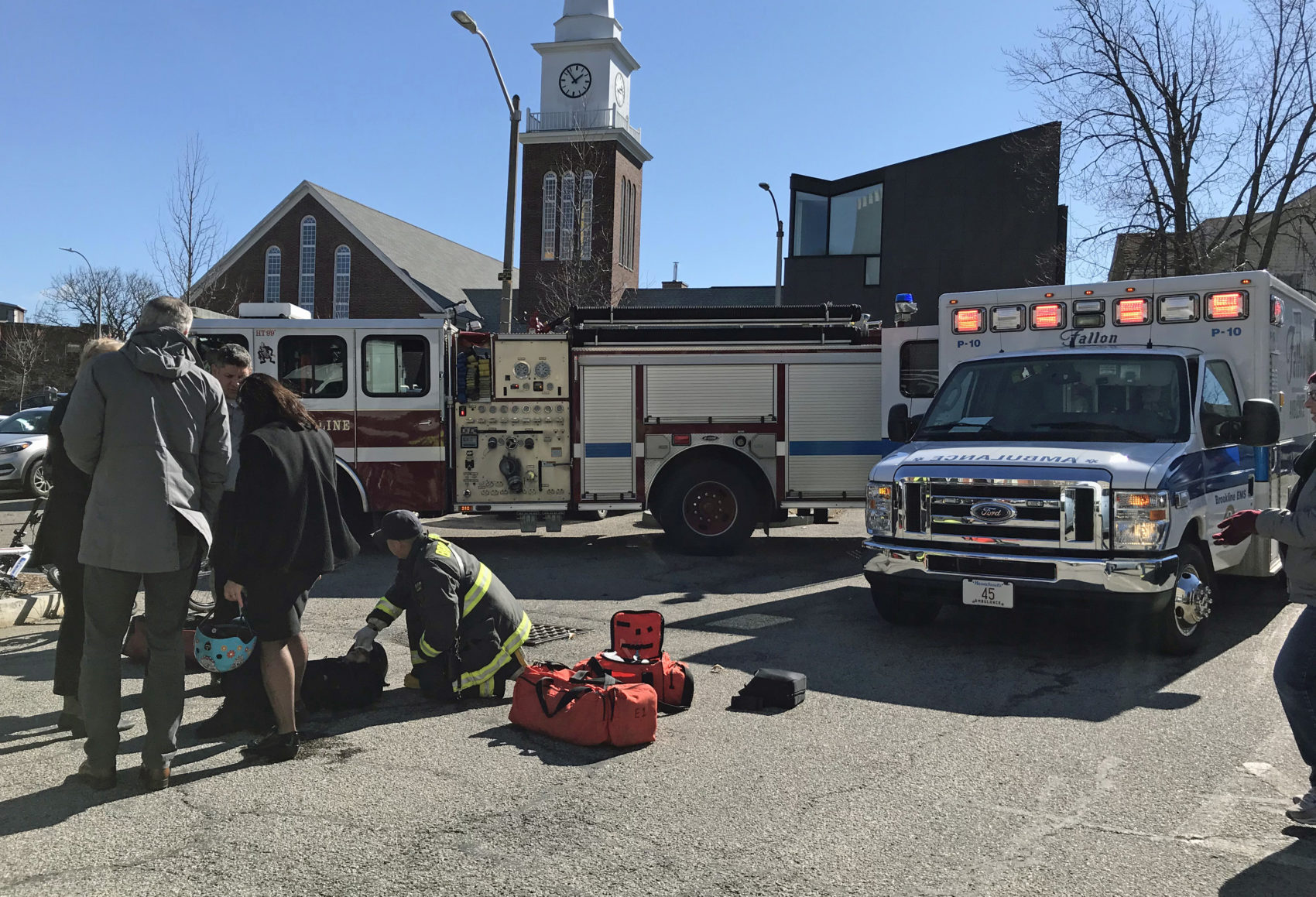 First responders treated a woman after an accident during a launch event for electric scooters in Brookline April 1. (Callum Borchers/WBUR)