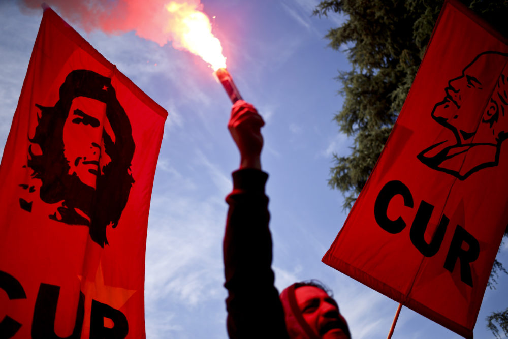 """A man holds a flare, flanked by banners depicting Cuban revolutionary heroes Ernesto """"Che"""" Guevara"""" and Jose Marti, during the annual May Day march, in Santiago, Chile, May 1, 2018. (Esteban Felix/AP)"""