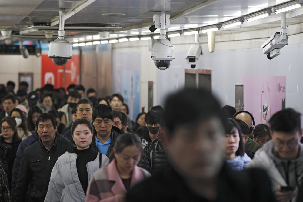 Commuters walk by surveillance cameras installed near a subway station in Beijing, Feb. 26, 2019. The Chinese government has used facial recognition and other technology to tighten control over society. (Andy Wong/AP)