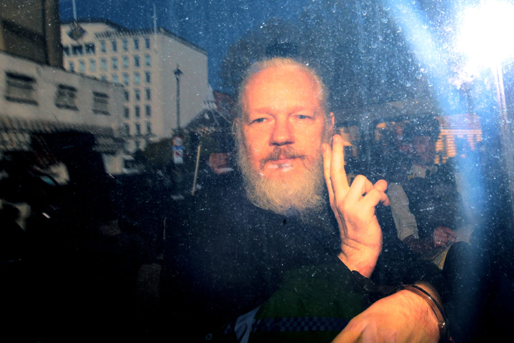 Julian Assange gestures to the media from a police vehicle on his arrival at Westminster Magistrates court on April 11, 2019 in London, England. (Jack Taylor/Getty Images)