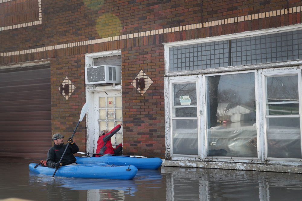 Residents try to enter their business by kayak on March 20, 2019 in Hamburg, Iowa. (Scott Olson/Getty Images)