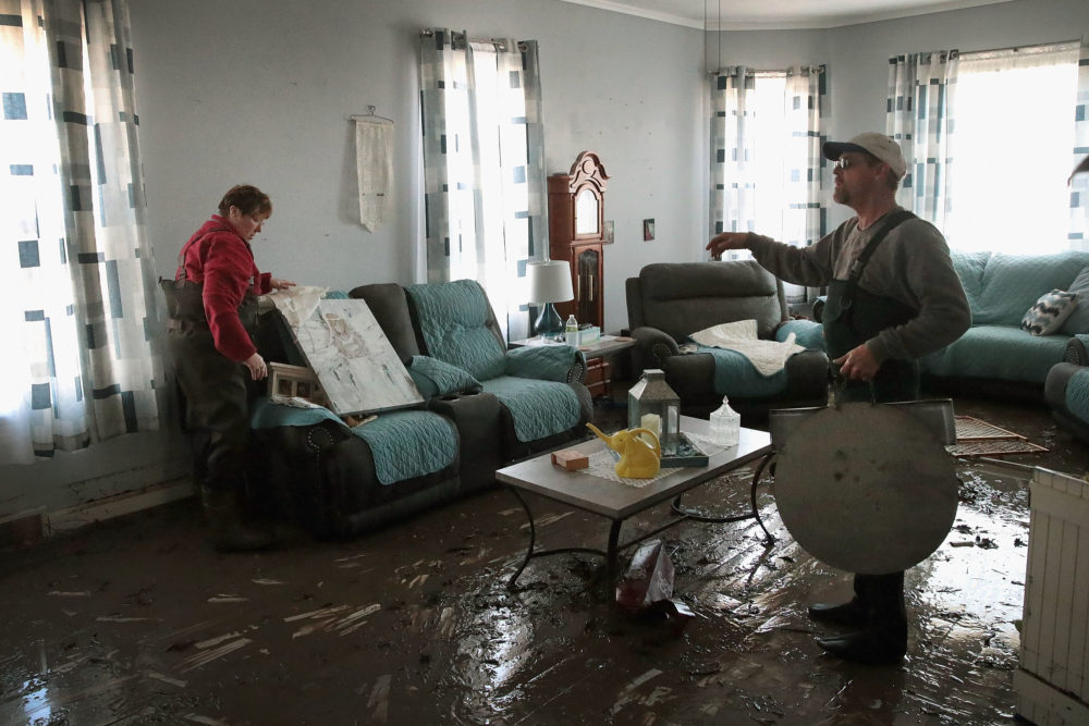 Bill Peeler (right) helps his friend Kathy Drummond remove items from her flooded home on March 20, 2019 in Hamburg, Iowa. (Scott Olson/Getty Images)