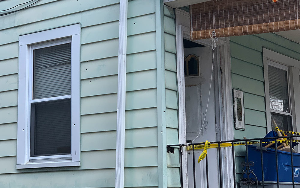 Bullet holes and police tape are seen on the side of the Mattapan home. (Simon Rios/WBUR)