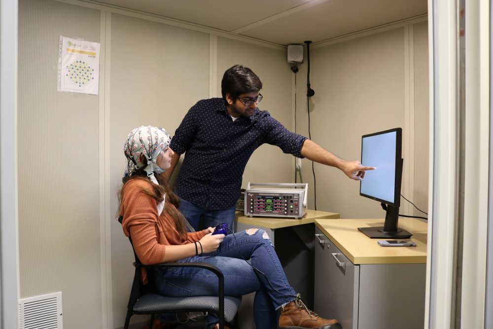 A young woman wears the skull cap with electrodes while performing a working memory test. (Courtesy of Rob Reinhart/BU)